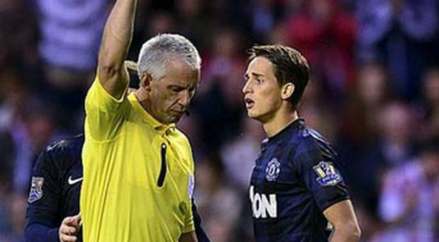 Referee Chris Foy books Manchester United's Adnan Januzaj during the Barclays Premier League match at The Stadium of Light, Sunderland.