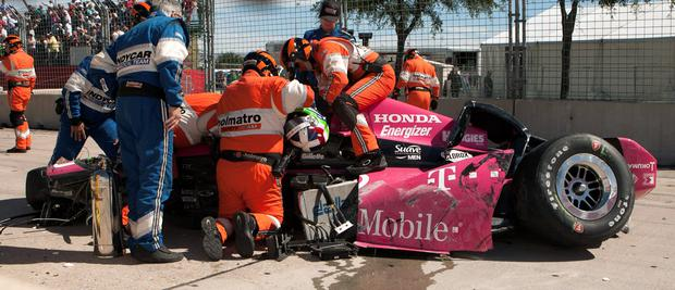 Safety team members work to remove Dario Franchitti, of Scotland, from his car after a crash during the second IndyCar Grand Prix of Houston