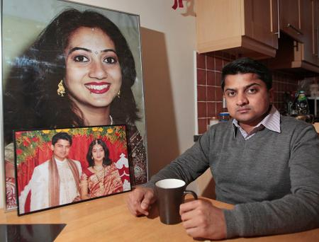 Pavreen Halapannar sits with a photograph of his wife Savita