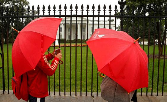 With few options open to tourists due to the federal government shutdown, a couple brave relentless rain to see the White House in Washington today