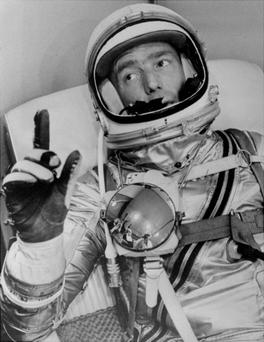 Astronaut Scott Carpenter gestures with one hand after donning his space suit in Hangar S prior to being shot into orbit at Cape Canaveral in 1962