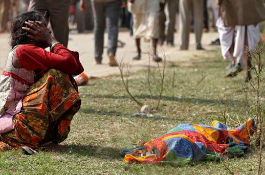 A woman cries next to the body of a victim killed in a stampede near Ratangarh temple, in Datia district in the central Indian state of Madhya Pradesh