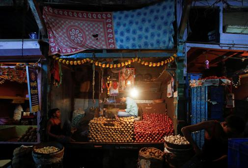 Vendors wait for customers at a stall at a wholesale food market in Mumbai