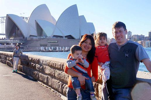 Phoumalaysy Rhodes, second left, and her husband Gavin Rhodes, right, hold their children Manfred and Jadesuda, second right, near the Sydney Opera House in Sydney, Australia