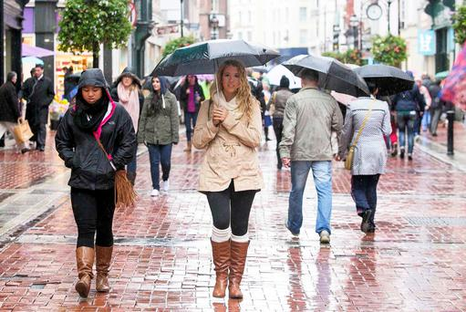 18/10/2013 Members of the public brave the bad weather in Dublin's city centre. Photo: Gareth Chaney Collins