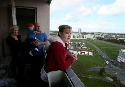 Teresa Freeman, one of the last remaining residents in the Ballymun flats, on the balcony of her flat on the top floor of the 15 storey Joseph Plunkett tower in Dublin with her daughter Donna Freeman with her partner Martin Grant and son Luke (2 years old)