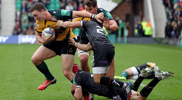 Northampton's George North is tackled by Ospreys Richard Fussell and Tito Tebaldi during the Heineken Cup