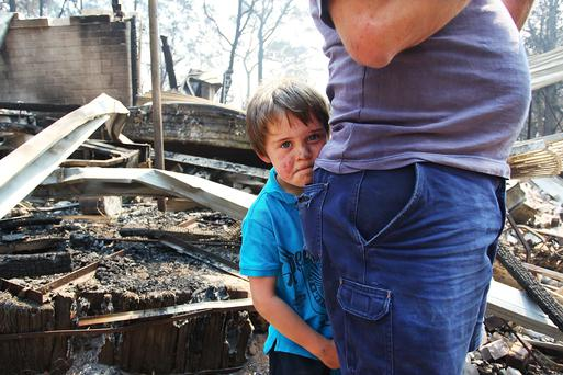 SYDNEY, AUSTRALIA - OCTOBER 21: Lyndon Dunlop stands by his father as they inspect the damage to his grandparent's home of 41 years destroyed by bushfire on October 21, 2013 in Winmalee, Australia. One man has died and hundreds of properties have been destroyed in bushfires that are devastating the Blue Mountains and Central Coast regions of New South Wales. (Photo by Lisa Maree Williams/Getty Images)
