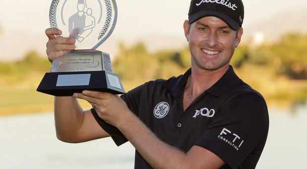 Webb Simpson holds up the championship trophy after winning in the final round of the STPC Summerlin tournament in Las Vegas