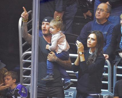 David Beckham, Harper Beckham and Victoria Beckham attend a hockey game between the Calgary Flames and the Los Angeles Kings at Staples Center on October 21, 2013 in Los Angeles, California. (Photo by Noel Vasquez/Getty Images)
