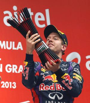 Red Bull Formula One driver Sebastian Vettel of Germany raises his trophy on the podium after winning the Indian F1 Grand Prix