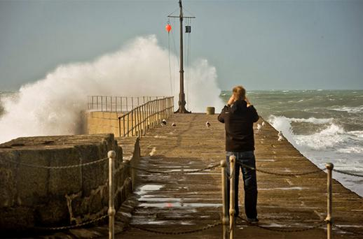 A man takes photographs of huge breaking waves on the harbour at Porthleven, Cornwall, as England and Wales face a battering from the worst storm in five years, forecasters warn. Photo: PA