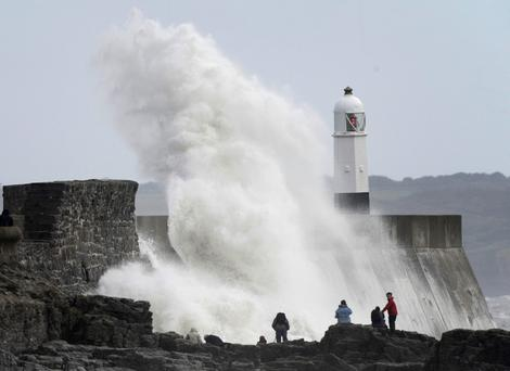 People watch as waves crash against the harbour wall at Porthcawl in south Wales October 28, 2013. Britain's strongest storm in a decade battered southern regions on Monday, forcing hundreds of flight cancellations, cutting power lines and disrupting the travel plans of millions of commuters. Winds of up to 99 miles per hour (160 km per hour) lashed southern England and Wales in the early hours of Monday, shutting down rail services in some areas during rush hour. REUTERS/Rebecca Naden (BRITAIN - Tags: ENVIRONMENT SOCIETY DISASTER)