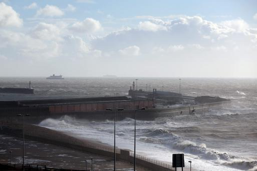 DOVER, UNITED KINGDOM - OCTOBER 28: Ferries wait beyond the harbour wall as large waves, produced by storm force winds, break on the shore on October 28, 2013 in Dover, England. Approximately 220,000 homes are without power and two deaths have been recorded after much of southern England has been affected by a severe storm. Transport links on road, rail, air and sea have been severely disrupted by hurricane-force winds that have almost reached 100 mph in places.. (Photo by Oli Scarff/Getty Images)