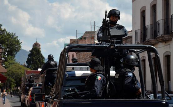 A federal police officer, part of a patrol, mans a weapon atop a vehicle in Morelia