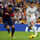 Real Madrid's Gareth Bale runs with the ball past Barcelona's Gerard Pique during their Spanish first division El Clasico soccer match at Nou Camp stadium in Barcelona