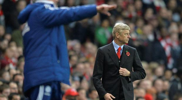 Arsenal's manager Arsene Wenger (R) watches as Chelsea's manager Jose Mourinho points during their English League Cup fourth round soccer match at Emirates Stadium in London