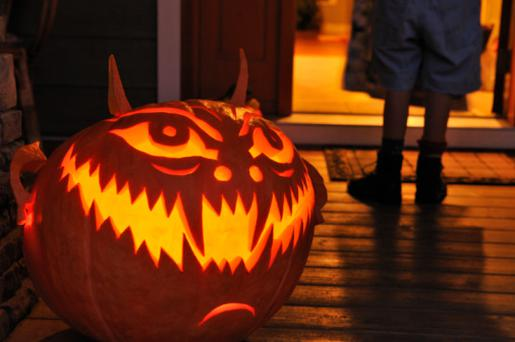 Jack-o'-lantern on porch with child trick or treating at door on Halloween or All Hallows Eve