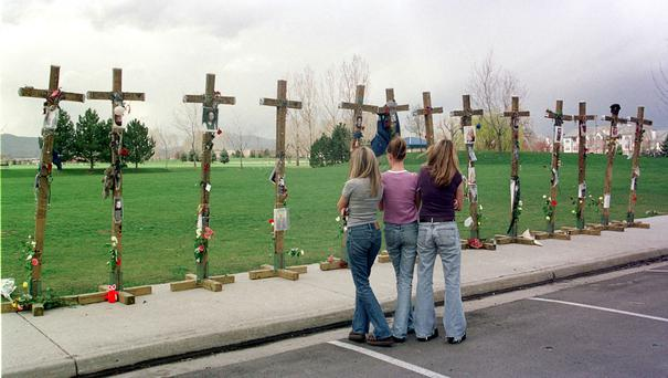 Columbine High School students look at the 13 crosses memorialising those killed at their school
