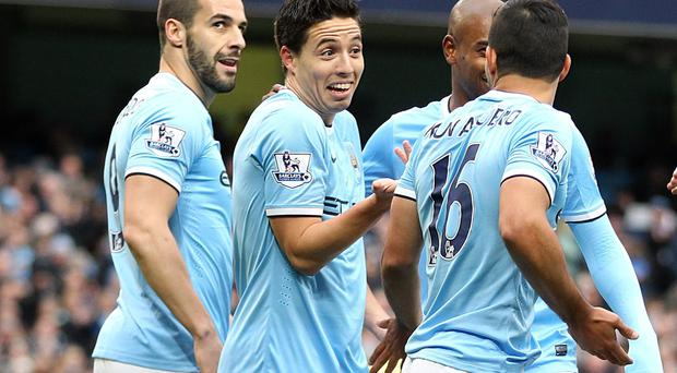 Manchester City's Sergio Aguero (right) takes the plaudits from team-mates after his shot comes off of Norwich City's Bradley Johnson to give City the lead