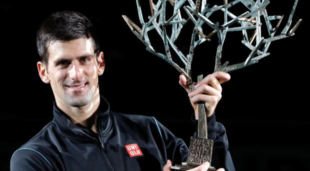 Novak Djokovic of Serbia holds his trophy after winning his men's singles final match against David Ferrer of Spain at the Paris Masters men's singles tennis tournament
