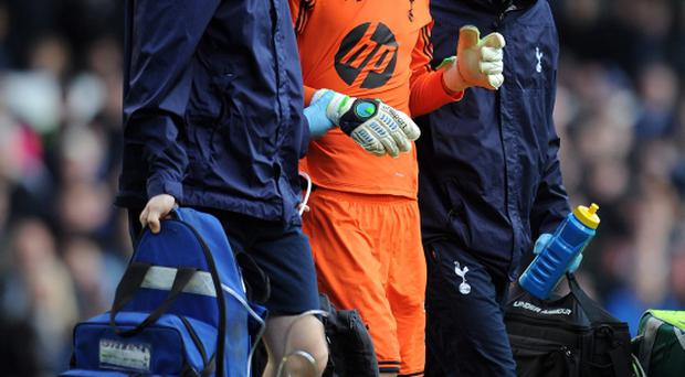 Hugo Lloris of Tottenham Hotspur leaves the field through injury yesterday but was brought back on