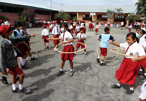 Students wearing masks to protect themselves from volcanic ash from Sunday's Mount Sinabung eruption, as they play with rattan rings at their school at Tiganderket village in Karo district, Indonesia's north Sumatra province
