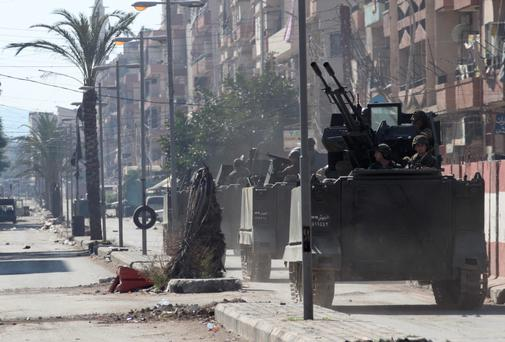 Lebanese army soldiers ride on their military vehicles after being deployed to tighten security following days of clashes between Sunni Muslims and Alawites in the northern port city of Tripoli