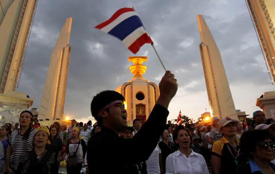 A protester waves a Thai national flag as he joins others in a rally at the Democracy Monument in central Bangkok