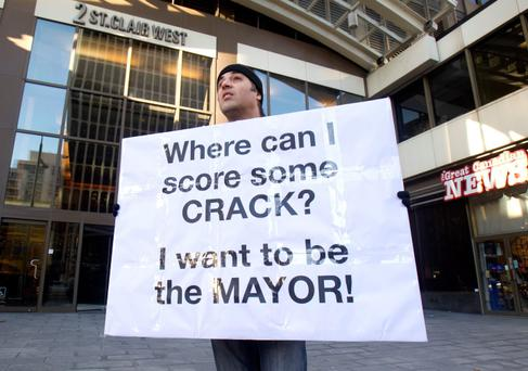 Nic Bibassis from Toronto holds a sign as Toronto Mayor Rob Ford (not seen) attends his weekly radio show at News Talk 1010 in Toronto