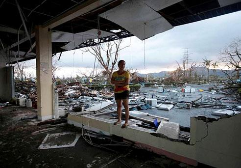 A woman stands amidst the devastation brought about by Typhoon Haiyan at Tacloban city, central Philippines.