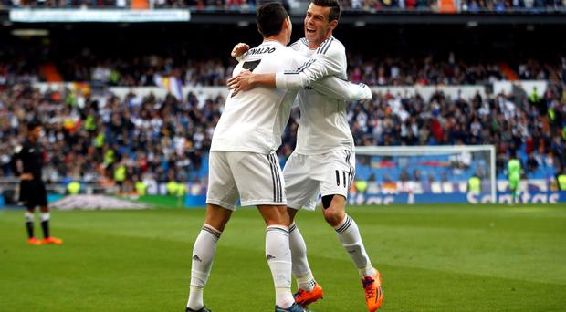 Real Madrid's Cristiano Ronaldo (L) is congratulated by his team mate Gareth Bale after scoring his first goal against Real Sociedad during their Spanish first division soccer match at Santiago Bernabeu stadium in Madrid November 9, 2013. REUTERS/Sergio Perez (SPAIN - Tags: SPORT SOCCER)