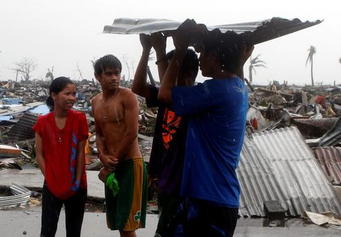 A couple (L) asks fellow typhoon victims where to get relief supplies after Super Typhoon Haiyan battered Tacloban city in central Philippines