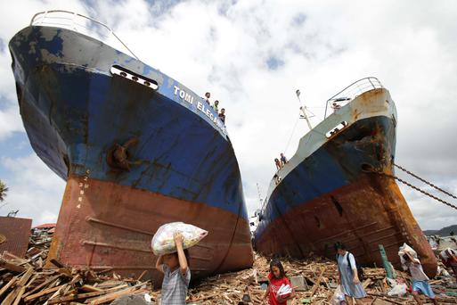 Survivors pass by two large ships after they were washed ashore by strong waves caused by Typhoon Haiyan in Tacloban city, Leyte province