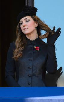 The Duchess of Cambridge plays with her hair as she stands in a balcony overlooking Whitehall's Cenotaph, in central London, prior to the annual Remembrance Sunday service