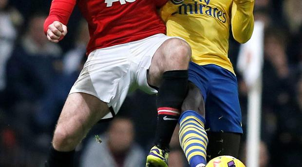 Manchester United's Wayne Rooney (L) challenges Arsenal's Bacary Sagna