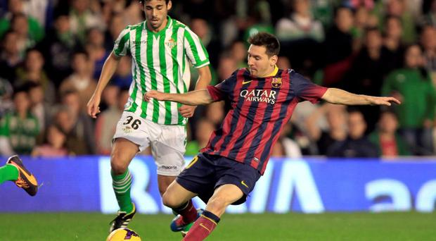 Barcelona's Lionel Messi (R) is challenged by Real Betis' Jose Antonio Caro during their Spanish First Division soccer match at Benito Villamarin stadium in Seville yesterday