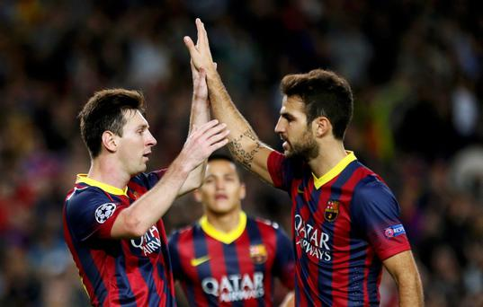 Barcelona's Lionel Messi (L) is congratulated by team mate Cesc Fabregas after scoring his second goal against AC Milan during their Champions League soccer match at Nou Camp stadium in Barcelona November 6, 2013. REUTERS/Gustau Nacarino (SPAIN - Tags: SPORT SOCCER)