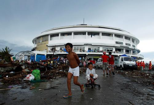 Children play outside the Tacloban City Convention Center, which has become a makeshift refuge center for displaced people after Super Typhoon Haiyan battered Tacloban city in central Philippines