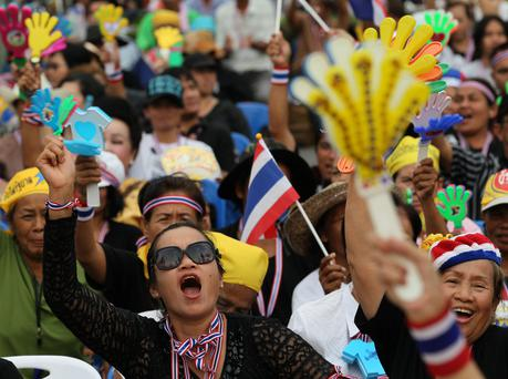 Anti-government protesters wave clapping tools during a rally against a political amnesty bill in Bangkok, Thailand
