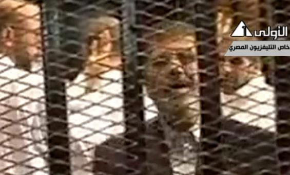This image made from video broadcast on Egyptian State Television shows ousted President Mohammed Morsi speaking from inside a mesh cage as he stands with other defendants during a court hearing at a police academy compound in Cairo