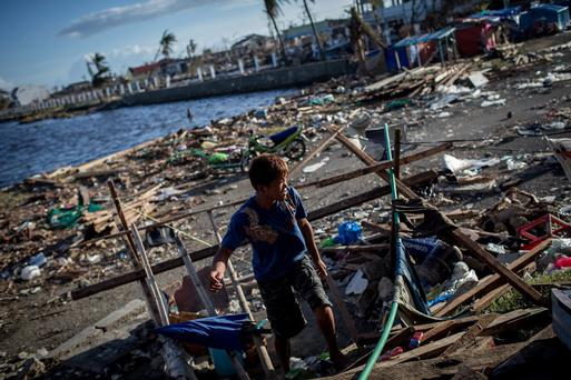 A man works on building a temporary shelter outside the Tacloban Stadium on November 15, 2013 in Leyte, Philippines. Typhoon Haiyan which ripped through Philippines over the weekend has been described as on of the most powerful typhoons ever to hit land, leaving thousands dead and hundreds of thousands homeless.