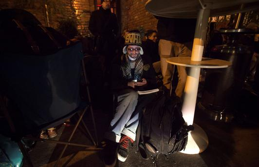 A man sits while waiting in line for Sony Playstation 4s to go on sale at a special sale event put on by Sony at the Standard Hotel in New York