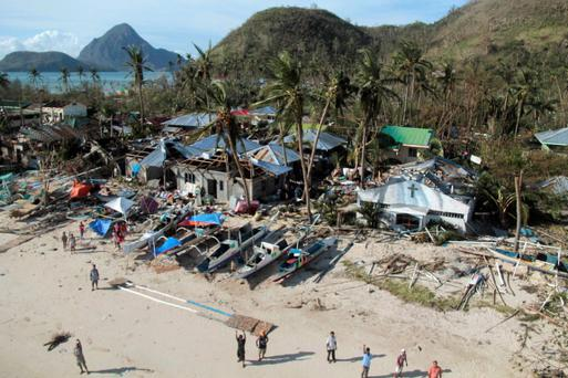 An aerial view shows damaged houses, as residents wave for help after Typhoon Haiyan hit a village in Panay island, in northern Iloilo Province, central Philippines