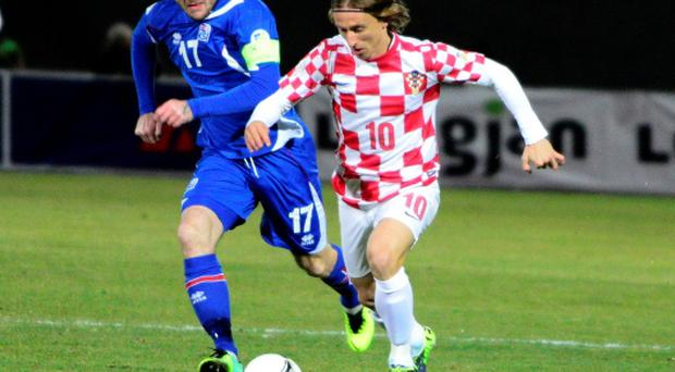 Luka Modric of Croatia (R) challenges Aron Gunnarsson of Iceland during their 2014 World Cup playoff soccer match in Reyjkavik