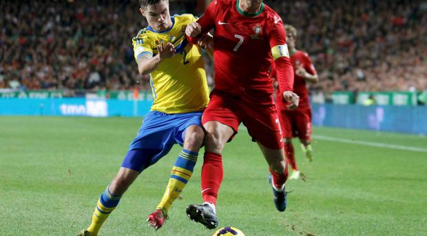Portugal's Cristiano Ronaldo (R) and Sweden's Mikael Lustig challenge for the ball during their 2014 World Cup first leg qualifying playoff soccer match at Luz stadium in Lisbon November 15, 2013. REUTERS/Rafael Marchante (PORTUGAL - Tags: SPORT SOCCER WORLD CUP)