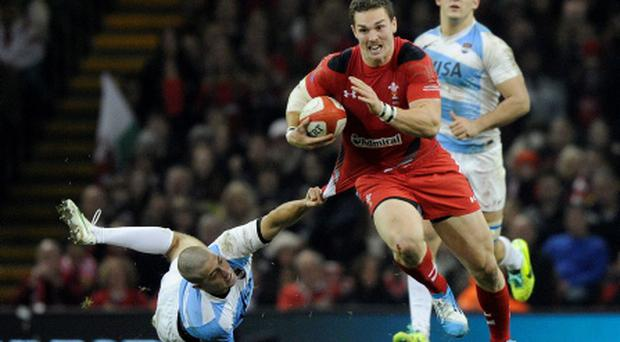 Wales' George North (C) is tackled by Argentina's Santiago Cordero