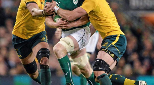 Paul O'Connell, Ireland, is tackled by Rob Simmons, left, and Ben Mowen