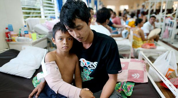 Mal Aron Antivo (11) is comforted by his brother Jerric after the typhoon struck his home town of Tacloban on the Island of Leyte, Philippines in the ward of the hospital Vincente Sotto in Cebu, capital city of Cebu Island.