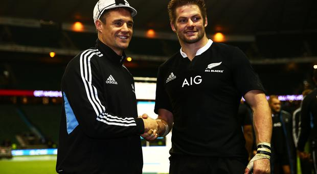 Dan Carter of New Zealand shakes hands with Richie McCaw of New Zealand (R) after receiving his 100th cap during the QBE International match between England and New Zealand at Twickenham Stadium on Saturday